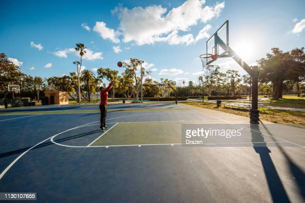 latino guy shooting basketball on the court in usa in summer - shooting baskets stock pictures, royalty-free photos & images