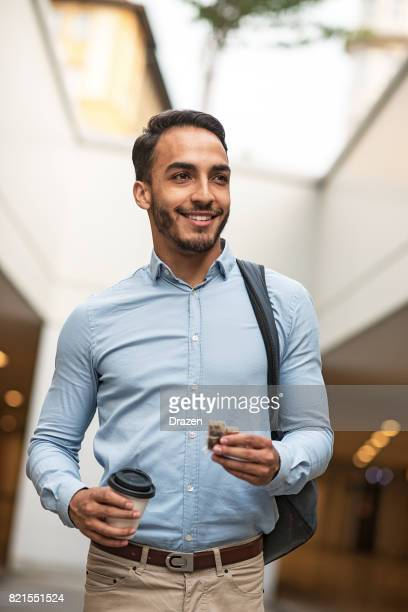 Latino man going to work and eating chocolate protein bar
