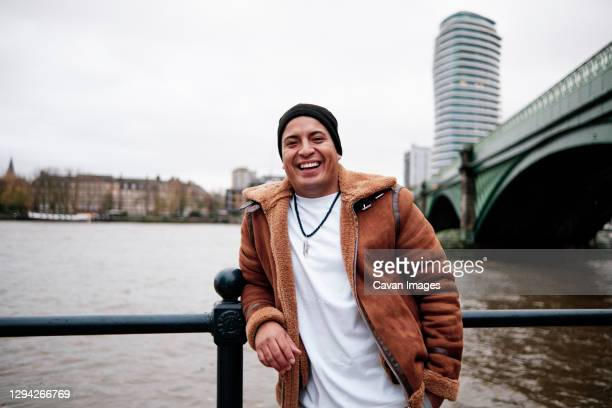 latino man grinning at the camera outside next to the river - emigration and immigration stock pictures, royalty-free photos & images
