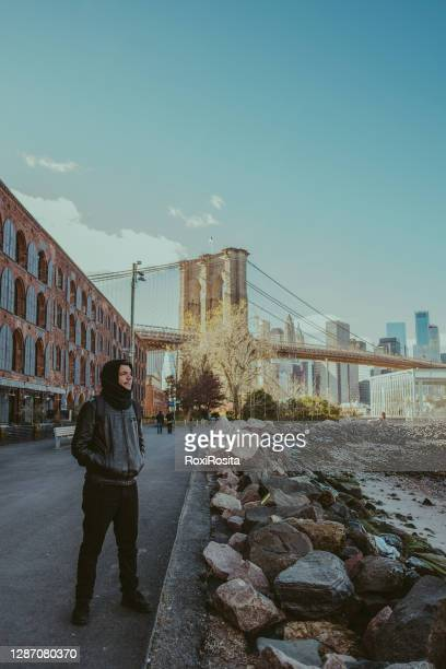 latino man in dumbo in front of the brookyn bridge - new york city - brooklyn new york stock pictures, royalty-free photos & images