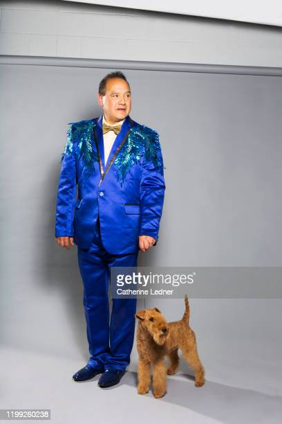 latino man in fancy blue suit and lakeland terrier show dog on grey seamless - dog show stock pictures, royalty-free photos & images