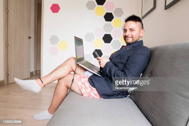 latino man is at home working dressed in a jacket and tie and at the bottom casual shorts - shorts stock pictures, royalty-free photos & images