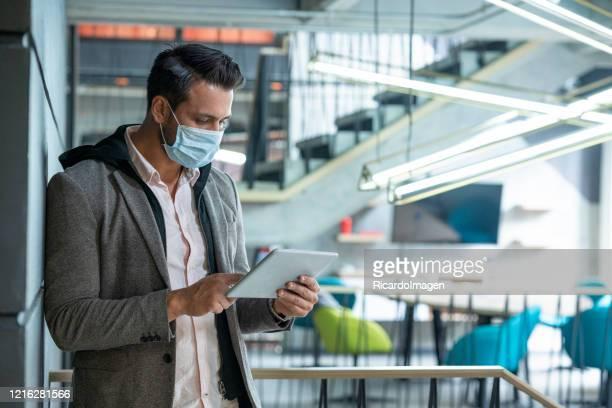 ラテン系の男性は、彼のフェイスマスクを着用して歩いて、タブレットを通して仕事をチェックする会社の廊下の一つです - リスク管理 ストックフォトと画像