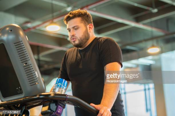 latino man of average age of 29 years on elliptical exercises - 25 29 years stock pictures, royalty-free photos & images