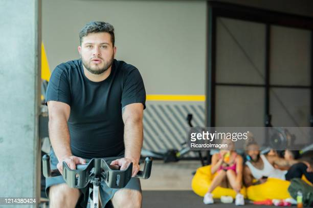 latino man of average age of 29 years on static biscleta exercises - 25 29 years stock pictures, royalty-free photos & images