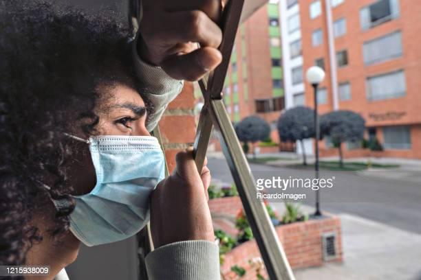 ラテン系の男はマスクを着用して彼の家の窓の外に彼の家を覗く - ボゴタ ストックフォトと画像
