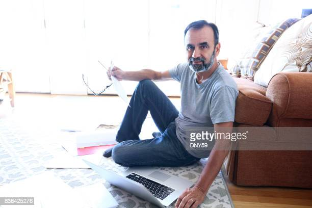 Latino Man Sits On Floor Leaning Against Couch While Working From Home