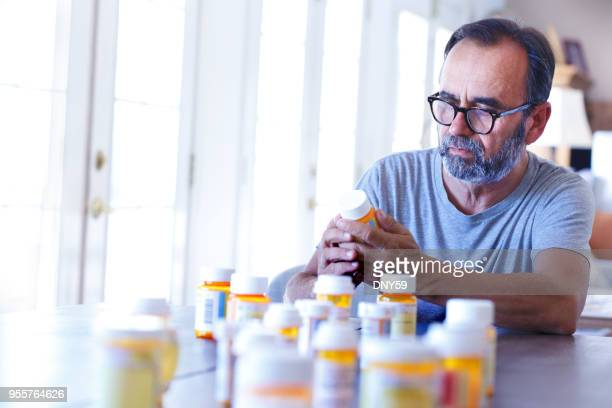 latino man sitting at table sorting through prescrption medications - pill bottle stock pictures, royalty-free photos & images