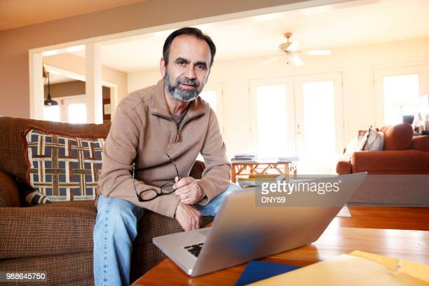 latino man sitting in chair at home while working on his computer - 50 59 years stock pictures, royalty-free photos & images