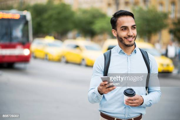Latino Mann mit mobile app Crowdsourcing-Taxi rufen