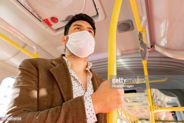 hombre latino que usa el transporte público en tiempo pandémico - colombia fotografías e imágenes de stock