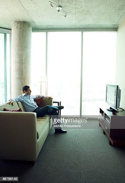 latino man watching television - onderdeel van een serie stockfoto's en -beelden