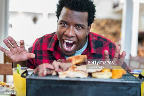 latino man with afro hair and brown skin, approximately 29 years old, faces a barbecue with meat sausage, looks at the camera and opens his mouth - 25 29 years stock pictures, royalty-free photos & images