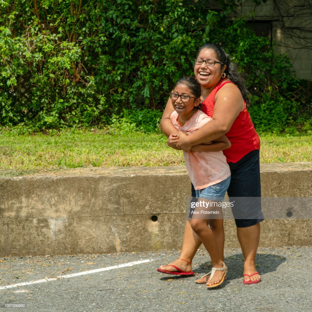 Latino, Mexican-American body-positive woman hugging her daughter outdoor : Stock Photo