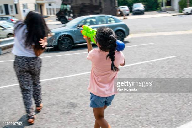 latino, mexican-american kids, girls of different ages, having fun, splashing and playing with a water gun outdoor - alex potemkin or krakozawr latino fitness stock photos and pictures