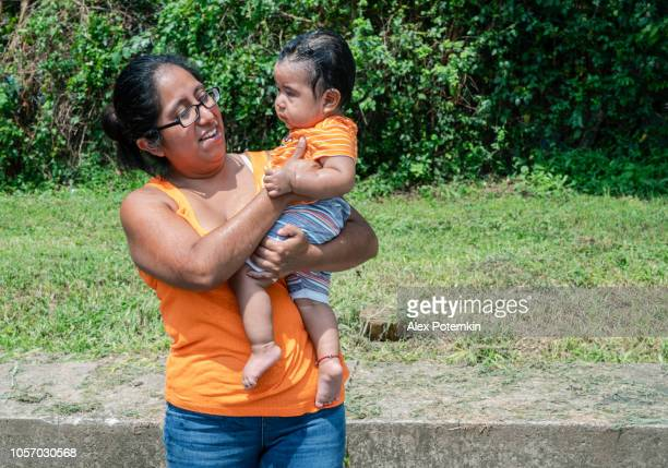 latino, mexican-american mother holding his little son outdoors - alex potemkin or krakozawr latino fitness stock photos and pictures