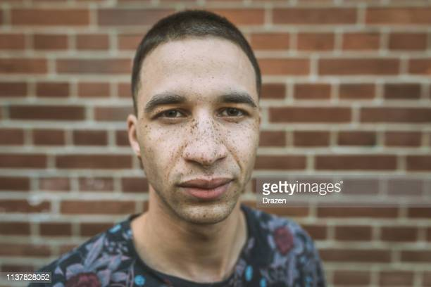 latino millennial generation man near the brick wall - masculinity stock pictures, royalty-free photos & images