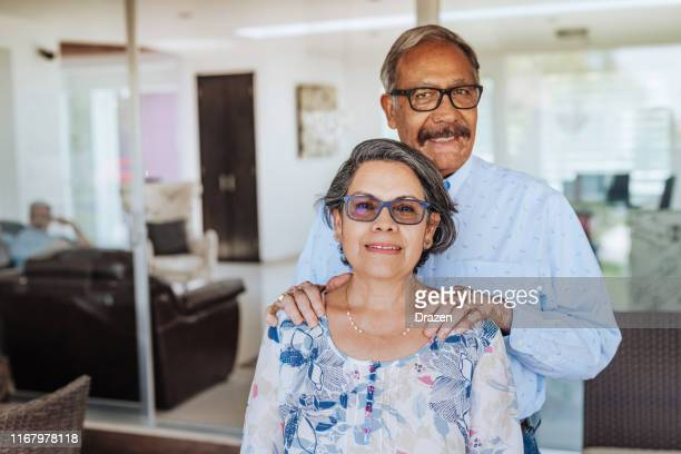 latino senior couple with eyeglasses enjoying retirement with loved ones. - family at home stock photos and pictures