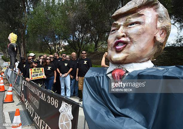 Latinos teamsters and their supporters pose beside an effigy of Donald Trump during protests against Trump and other Republican president hopefuls...
