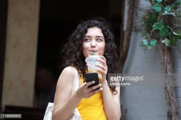 a latinx female millennial smiles while holding a cell phone and drinking an iced coffee, on a summer day in new york city. - one young woman only stock pictures, royalty-free photos & images
