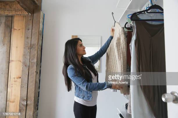 a latinx millennial woman with long brown hair, looks through her closet for something to wear. - casacca foto e immagini stock