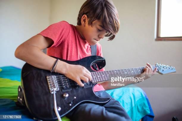 自宅でエレキギターを弾くことを学ぶラテン語思春期前の子供 - 爪弾く ストックフォトと画像