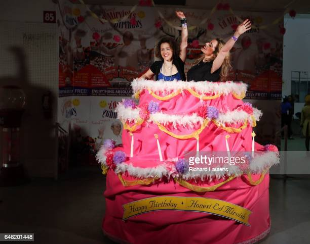 Latisha Pederson )left) and Jenny Da Silva get into the party spirit in a large Ed Mirvish birthday cake at the party. The famed Honest Ed's has one...