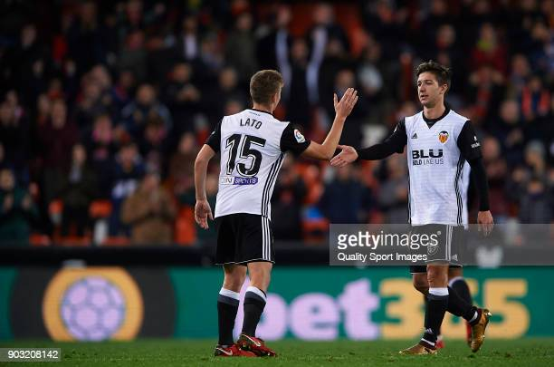Lato of Valencia greets his teammate Luciano Vietto during the Copa del Rey Round of 16 second Leg match between Valencia CF and UD Las Palmas on...