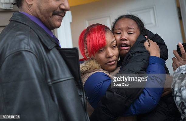 LaTonya Jones the daughter of Bettie Jones hugs a crying child during a vigil outside her home on December 27 2015 in Chicago Illinois Bettie Jones...