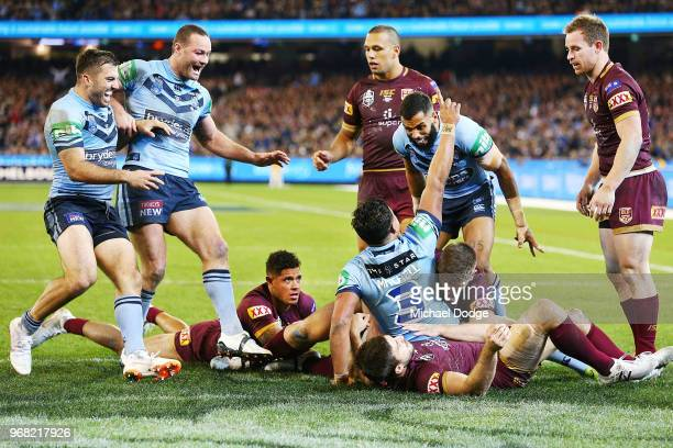Latrell Mitchell of the Blues celebrates after he scores a try against Ben Hunt of the Maroons during game one of the State Of Origin series between...