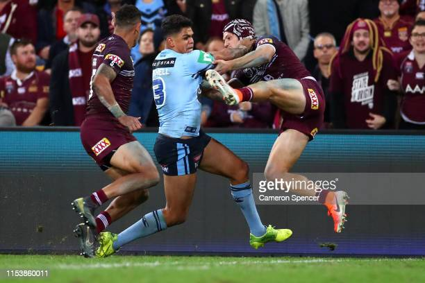 Latrell Mitchell of the Blues fends off Kalyn Ponga of Queensland during game one of the 2019 State of Origin series between the Queensland Maroons...