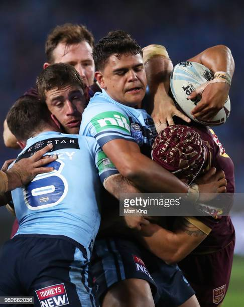 Latrell Mitchell of the Blues is tackled during game two of the State of Origin series between the New South Wales Blues and the Queensland Maroons...