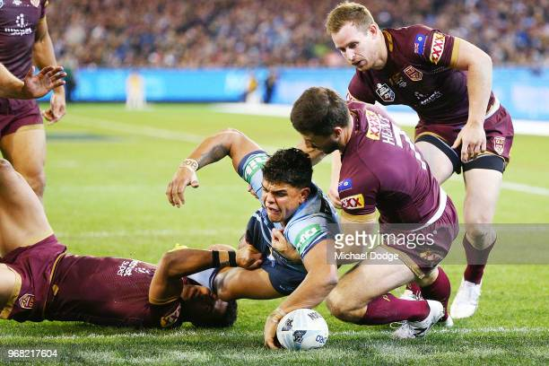 Latrell Mitchell of the Blues scores s try against Ben Hunt of the Maroons during game one of the State Of Origin series between the Queensland...