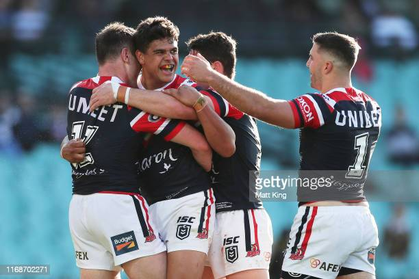 Latrell Mitchell of the Roosters celebrates with team mates after scoring a try during the round 22 NRL match between the Sydney Roosters and the New...
