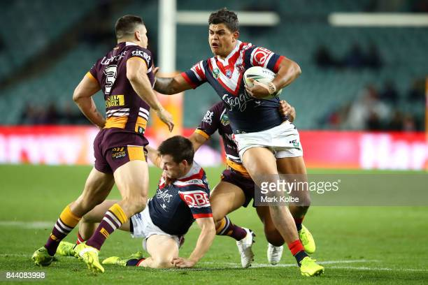 Latrell Mitchell of the Roosters fends away James Roberts of the Broncos as he breaks away to score a try during the NRL Qualifying Final match...
