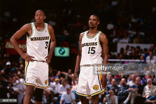 Latrell Sprewell and Donyell Marshall of the Golden State Warriors look on during a game played circa 1995 at the Oakland Coliseum in Oakland...