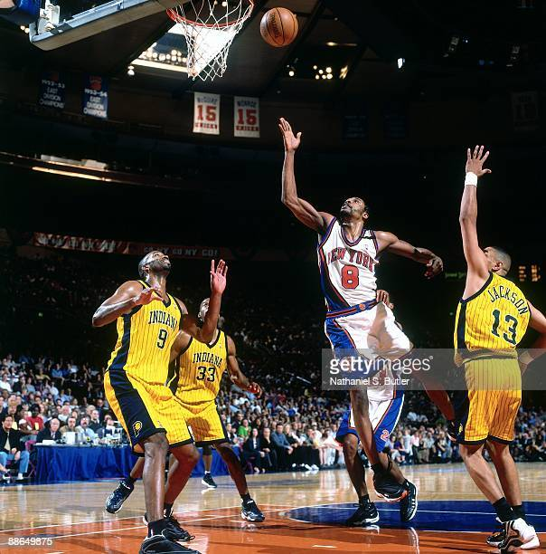 Latrell Sprewell of the New York Knicks shoots a layup against Derrick McKey and Mark Jackson of the Indiana Pacers in Game Three of the Eastern...