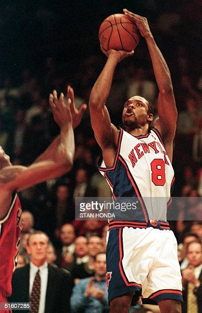 Latrell Sprewell of the New York Knicks shoots over Keith Askins of the Miami Heat as Miami coach Pat Riley watches during the third quarter of the...