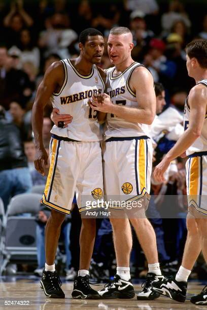 Latrell Sprewell#15 and Chris Mullin of the Golden State Warriors converse with one another during a break in the game against the Philadelphia 76ers...