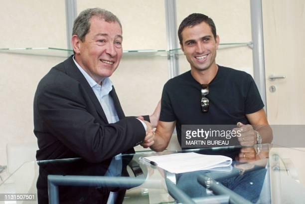 l'attaquant international portugais Pauleta serre la main du président du club de football du PSG Francis Graille le 10 juillet 2003 à Paris après la...