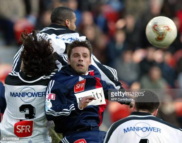l'attaquant parisien Cédric Fiorese est à la lutte avec le Lorientais Xavier Le Lan le 09 mars 2002 au Parc des Princes à Paris lors de la rencontre...