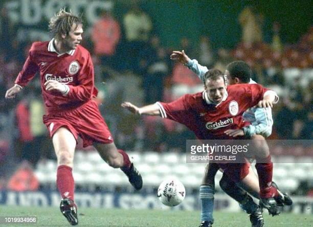 l'attaquant strasbourgeois David Conteh est aux prises avec les défenseurs anglais Jones et Kvarme le 04 novembre sur la pelouse du stade Anfielf...