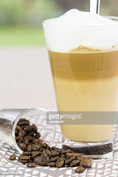 Latte Macchiato and glass of coffee beans on cloth