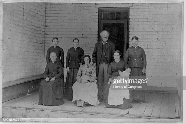 A Latter Day Saint poses on a porch with his mother and five wives 1885