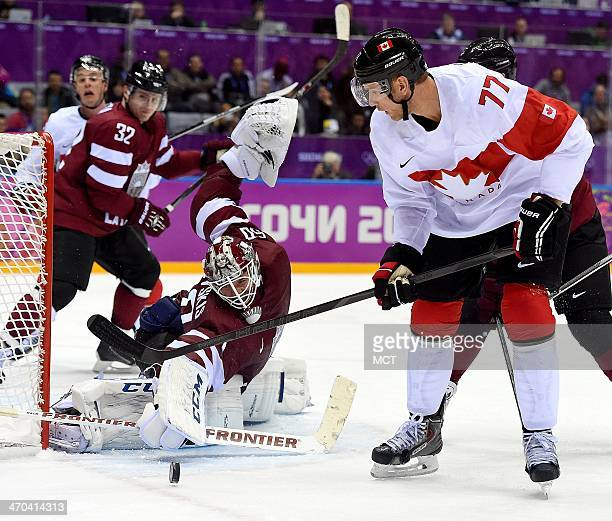 Latvia goalie Kristers Gudlevski stops a shot by Canada forward Jeff Carter during the third period in a men's hockey quarterfinal game at the Winter...