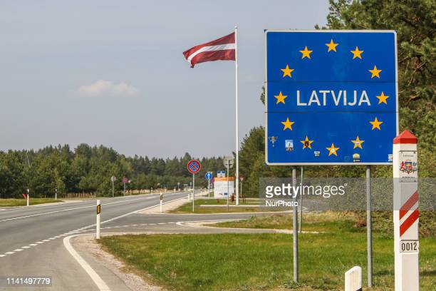 Latvia inscription on a sign with EU stars with with a Latvian flag in the background is seen on a Lithuania - Latvia Schengen Area border crossing...