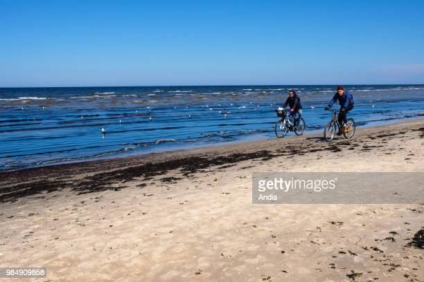 Jurmala Couple of walkers riding bikes on the beach in spring in front of the Baltic Sea