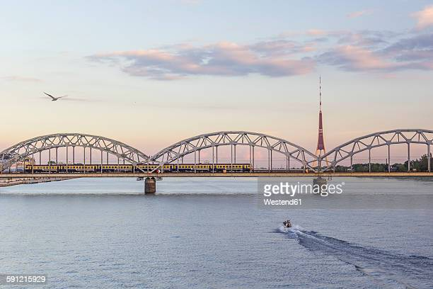 latvia, riga, railway bridge and tv tower at the daugava river in the evening - latvia stock pictures, royalty-free photos & images