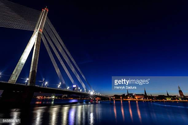 latvia, riga, river daugava, illuminated vansu bridge reflecting in river - latvia stock pictures, royalty-free photos & images