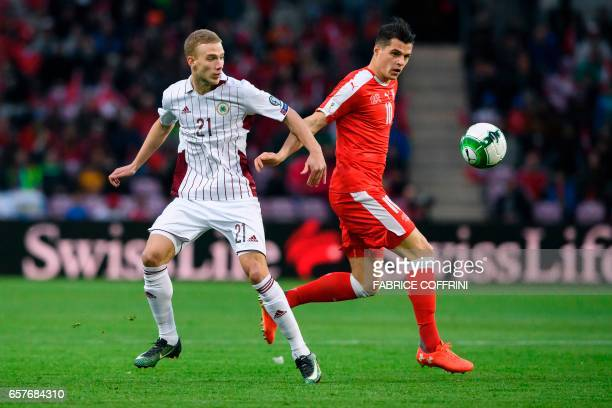 Latvian midfielder Glebs Kluskins vies with Swiss midfielder Granit Xhaka during the WC 2018 qualifying football match Switzerland vs Latvia on March...